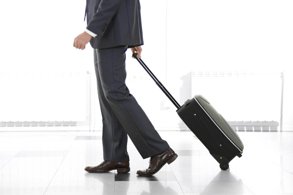 Man holding suitcase on light background