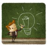 Businessman drawing a light bulb on a green chalkboard